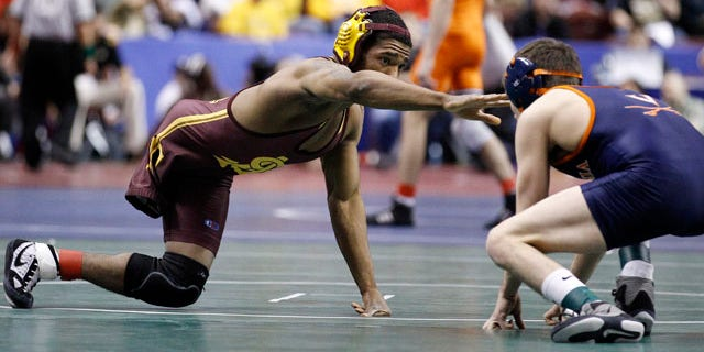 March 17, 2011: Arizona State's Anthony Robles, left, reaches for Virginia's Matthew Snyder during their 125-pound first round match at the NCAA Division I Wrestling Championships in Philadelphia.