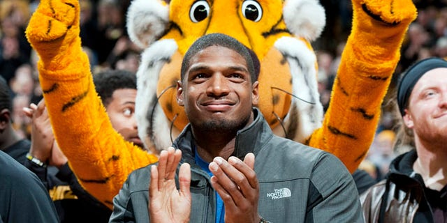 Feb. 15, 2014: Missouri's All-American defensive end Michael Sam claps during the Cotton Bowl trophy presentation at halftime of an NCAA college basketball game between Missouri and Tennessee.