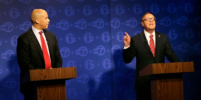 Oct. 4, 2013: Cory Booker (l.) looks on as Republican Steve Lonegan answers a question during their first debate of the U.S. Senate campaign in Trenton, N.J. Booker is Newark's two-term mayor. Lonegan is the former state director of a conservative advocacy group, Americans for Prosperity, and former mayor of Bogota, N.J.