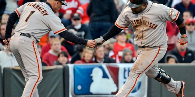 Oct. 10, 2012: San Francisco Giants' Pablo Sandoval is congratulated by third base coach Tim Flannery (1) after hitting a two-run home run against the Cincinnati Reds in the seventh inning of Game 4 of the National League division baseball series, in Cincinnati.