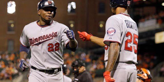 Minnesota Twins' Miguel Sano, left, fist-bumps teammate Byron Buxton after scoring on a bases-loaded walk to Eduardo Nunez during the fourth inning of a baseball game against the Baltimore Orioles, Friday, Aug. 21, 2015, in Baltimore. (AP Photo/Patrick Semansky)