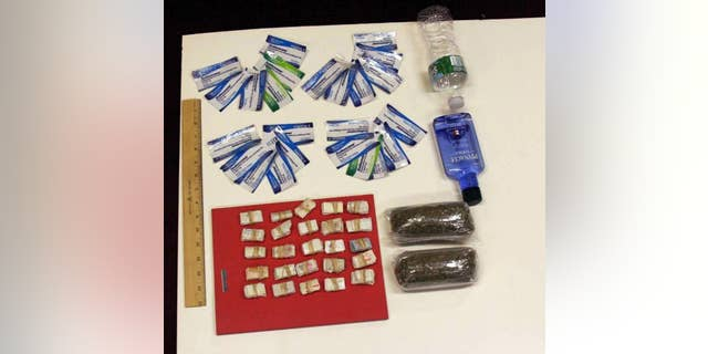 In this undated photo provided by the New York City Department of Investigation, contraband smuggled by an undercover investigator into Rikers Island jail facilities is shown. During six visits to the New York City jail, the investigator was able to get a plastic bag containing 250 glassine envelopes of heroin; one plastic bag containing 24 packaged strips of suboxone; two plastic bags containing a total weight of one half-pound of marijuana, 16 ounces of vodka in a water bottle, and one razor blade past the personnel at the security entrance. (AP Photo/New York City Department of Investigation)