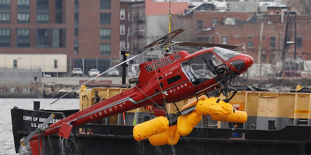 The wreckage of a chartered Liberty Helicopters helicopter that crashed into the East River is hoisted from the water in New York, U.S., March 12, 2018.