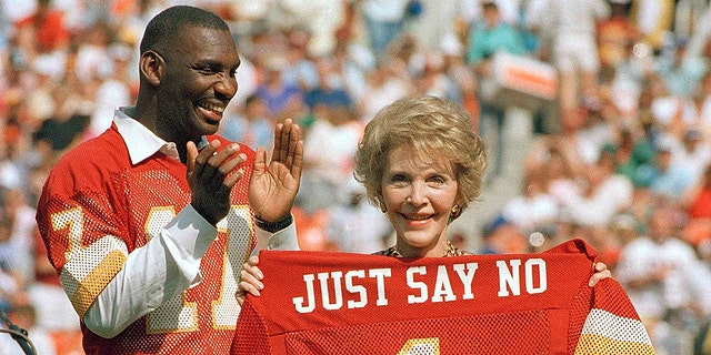 Washington Redskins quarterback Doug Williams stands behind First lady Nancy Reagan holding a jersey he gave her