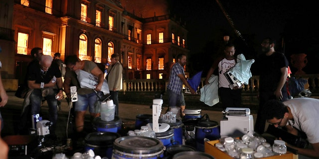 People work to rescue items during a fire at the National Museum of Brazil.