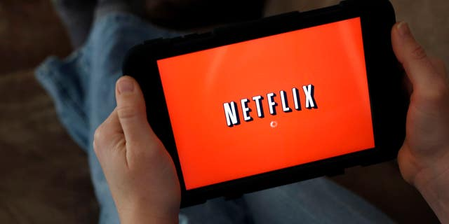 A person displays Netflix on a tablet in North Andover, Mass.