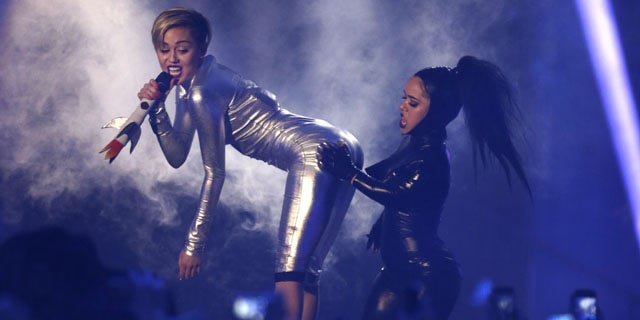 November 10, 2013: Miley Cyrus, left, and a dancer perform at the 2013 MTV Europe Music Awards in Amsterdam, Netherlands. (AP Photo/Peter Dejong)