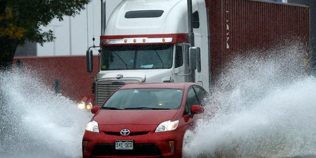 A motorist drives through flooding water in Portland, Maine.
