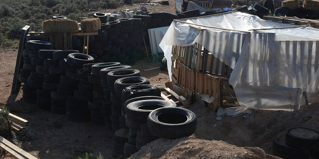 Tires form a wall at a squalid makeshift living compound in Amalia, New Mexico, on Friday, where five adults were arrested on child abuse charges and remains of a boy were found.