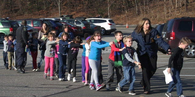 In this photo provided by the Newtown Bee, Connecticut State Police lead a line of children from the Sandy Hook Elementary School in Newtown, Conn. on Friday, Dec. 14, 2012 after a shooting at the school. (AP Photo/Newtown Bee, Shannon Hicks, File) MANDATORY CREDIT: NEWTOWN BEE, SHANNON HICKS