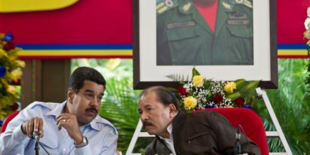 Under a portrait of the late Hugo Chavez, Venezuela's President Nicolas Maduro, left, talks with Nicaragua's President Daniel Ortega during the 8th Petrocaribe Summit in Managua, Nicaragua. (AP Photo/Esteban Felix, File)