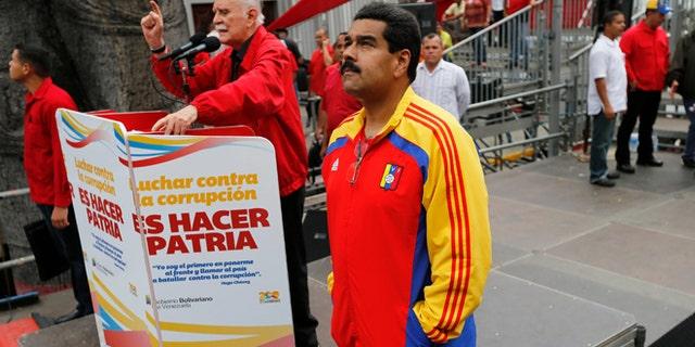 Venezuela's President Nicolas Maduro waits his turn to speak during a march against corruption, in Caracas, Venezuela, Aug. 3, 2013.