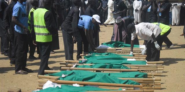 November 4, 2014: People prepare bodies of victims of a suicide bomb explosion for funeral in Potiskum, Nigeria. (AP Photo/Adamu Adamu)