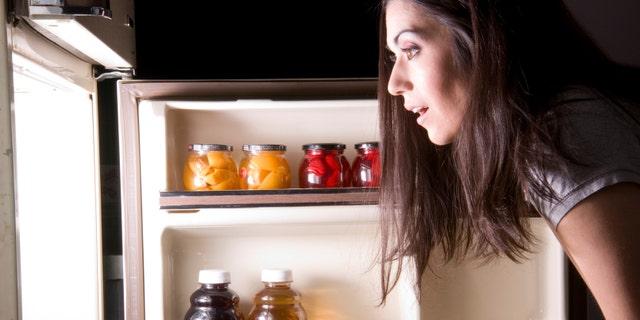 A woman raids the refrigerator late at night