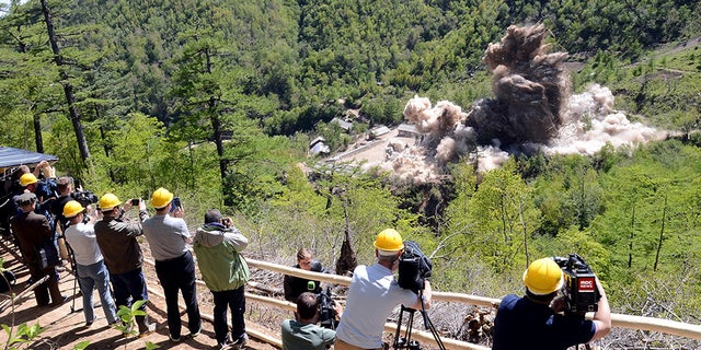 Onlookers wearing hard hats appear to film the demolition of the supposed nuclear test site.