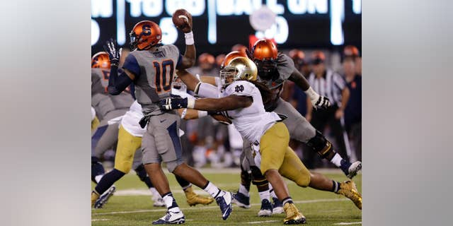 Notre Dame defensive lineman Sheldon Day, right, applies pressure on Syracuse quarterback Terrel Hunt (10) during the second half of an NCAA college football game, Saturday, Sept. 27, 2014, in East Rutherford, N.J. Notre Dame won 31-15. (AP Photo/Julio Cortez)