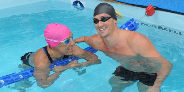 """Eleven-time Olympic medalist Ryan Lochte swims with Diana Nyad during her 48-hour continuous """"Swim for Relief"""" to support Hurricane Sandy recovery efforts in New York's Herald Square."""