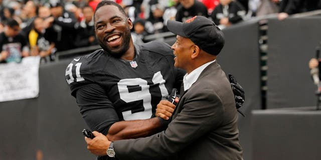 Dec 7, 2014; Oakland, CA, USA; Oakland Raiders defensive end Justin Tuck (91) meets with former NFL player Ronnie Lott before the start of the game against the San Francisco 49ers at O.co Coliseum. Mandatory Credit: Cary Edmondson-USA TODAY Sports