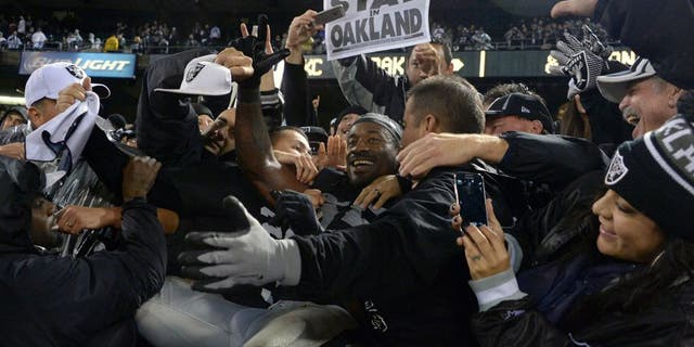 Nov 20, 2014; Oakland, CA, USA; Oakland Raiders lineabcker Sio Moore (55) celebrates with fans after the game against the Kansas City Chiefs at O.co Coliseum. The Raiders defeated the Chiefs 24-20. Mandatory Credit: Kirby Lee-USA TODAY Sports