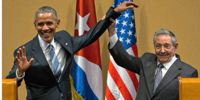 FILE - In this March 21, 2016 file photo, Cuban President Raul Castro, right, lifts up the arm of President Barack Obama at the conclusion of their joint news conference at the Palace of the Revolution, in Havana, Cuba. Donald Trumps pledge to undo Obamas detente with Cuba is provoking widespread anxiety among ordinary Cubans, who were paying little attention to the U.S. presidential campaign until now. (AP Photo/Ramon Espinosa, File)