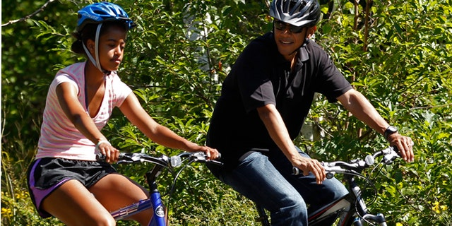 FILE: August 23, 2011: President Obama bikes with daughter Malia during their family vacation on Martha's Vineyard in Massachusetts.