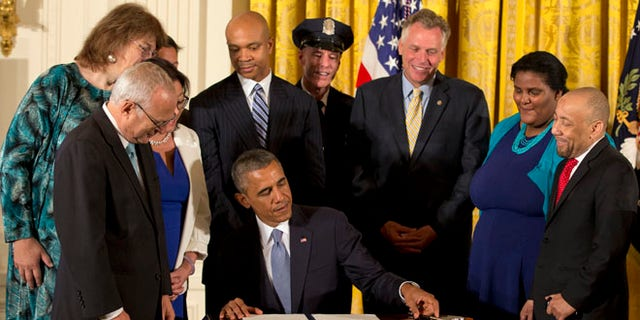 July 21, 2014: President Obama signs executive orders to protect LGBT employees from federal workplace discrimination in the East Room of the White House.