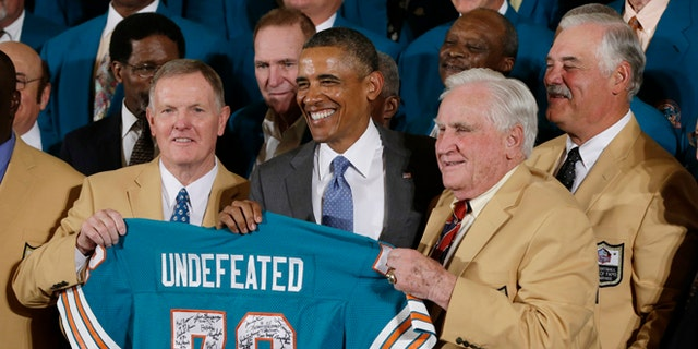 Former Miami Dolphins football quarterback Bob Griese, left, and Hall of Fame Dolphins Coach Don Shula, second from right, and Larry Csonka, right, pose for photographs with a signed team jersey during a ceremony in the East Room of the White House in Washington, Tuesday, Aug. 20, 2013, where the president honored the Super Bowl VII football Champion Miami Dolphins.