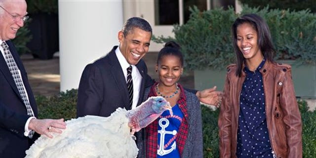 """Nov. 21, 2012: President Obama, with daughters Sasha, center, and Malia, right, carries on the Thanksgiving tradition of saving a turkey from the dinner table with a """"presidential pardon"""" at the White House."""