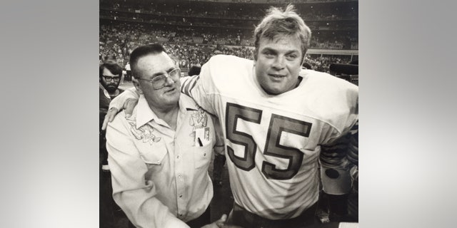 In this November 1981 file photo, New Orleans Saints coach Bum Phillips, left, gets an embrace from Houston Oilers center Cal Mauck, who played for Phillips until the coach was fired by the Oilers, at the Astrodome in Houston after an NFL football game.