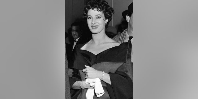 "FILE - In this March 4, 1954, file photo, actress Rita Gam stands in lobby of Longacre Theatre at opening of  ""The Burning Glass"" in New York."