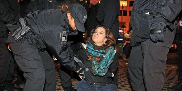 Dec. 10, 2011: Boston police officers remove an Occupy Boston protester from Dewey Square in Boston before dawn Saturday.