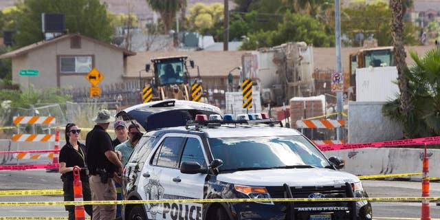 In this Sept. 6, 2015, photo, investigators stand by a Las Vegas Metro Police patrol vehicle after an officer in the vehicle was shot in Las Vegas. A man with a handgun walked up to the SUV as it was waiting at a red light and opened fire, striking one officer in the hand, authorities said. (Steve Marcus/Las Vegas Sun via AP) LAS VEGAS REVIEW-JOURNAL OUT; MANDATORY CREDIT