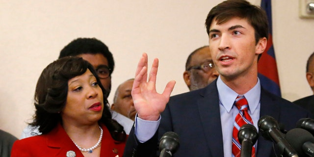 March 25, 2015: Oklahoma state Sen. Anastasia Pittman, left, D-Oklahoma City, stands with Levi Pettit, right, a former University of Oklahoma fraternity member caught on video leading a racist chant, during a news conference at Fairview Baptist Church in Oklahoma City.  (AP Photo/Sue Ogrocki)