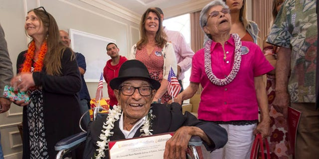 Alfonso Gonzales, 96, University of Southern California's oldest graduating Trojan receives his Bachelor of Science degree in zoology diploma from USC surrounded by family members, as part of the 2016 USC Commencement ceremony, on Friday, May 13, 2016 in Los Angeles. The World War II veteran thought he'd already graduated when he skipped commencement exercises in 1953 because of work obligations. He was founding a soil company that he ran for 55 years. But when relatives recently approached USC about getting a copy of his diploma, they learned he was one unit short. Although the school no longer offers a zoology major, it crafted an independent study course through the gerontology school that included reading, video assignments, visiting other classes, and writing a thesis about his life. (Gus Ruelas/USC via AP)