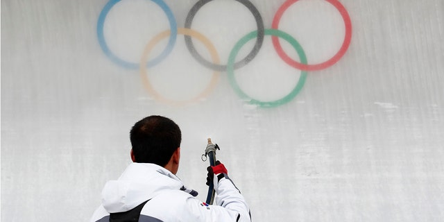 A worker sprays water on the Olympic rings at the Olympic Sliding Centre in Pyeongchang, South Korea.