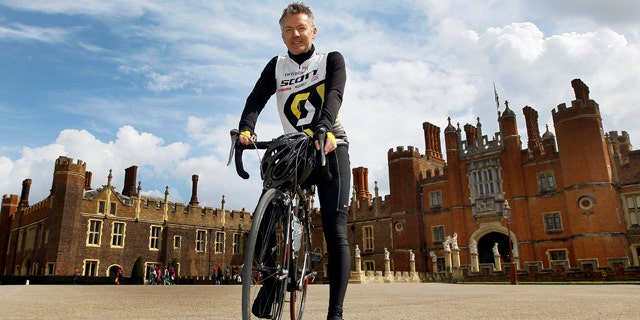 April 20, 2012: In this photo, Surrey County Councils Alan Flaherty, who has been involved in designing the Olympic road cycle course, and helping athletes to test it out, poses for a photograph in front of Hampton Court Palace, Hampton, England.