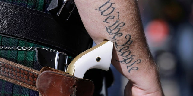 Scott Smith, a supporter of open carry gun laws, wears a pistol as he prepares for a rally in support of open carry gun laws at the Capitol, in Austin, Texas, Jan. 26, 2015.(Associated Press)