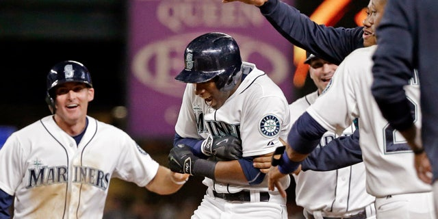 Aug. 11, 2015: Seattle Mariners' Austin Jackson, center, is mobbed by teammates after hitting in the game-winning run against the Baltimore Orioles in the 10th inning of a baseball game in Seattle. The Mariners won 6-5. (AP Photo/Elaine Thompson)