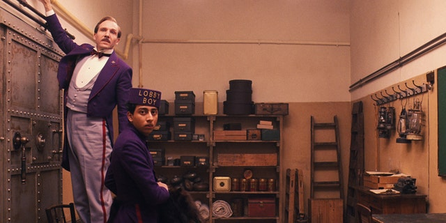"""This image released by Fox Searchlight shows Ralph Fiennes, left, and Tony Revolori in """"The Grand Budapest Hotel. """" The film is nominated for an Oscar Award for best feature. The 87th Annual Academy Awards will take place on Sunday, Feb. 22, 2015 at the Dolby Theatre in Los Angeles. (AP Photo/Fox Searchlight)"""