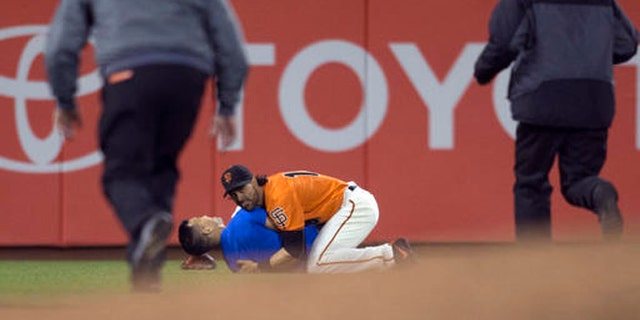 San Francisco Giants Angel Pagan (16) holds down a man who ran onto the field during the fourth inning of the Giants' baseball game against the Los Angeles Dodgers, Friday, Sept. 30, 2016, in San Francisco. (AP Photo/D. Ross Cameron)