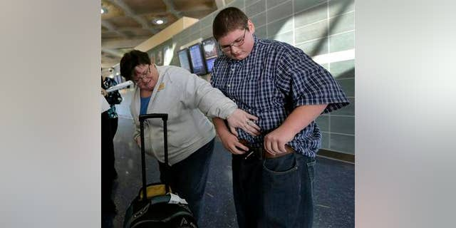 Dec. 21, 2012: Debbie Alexander checks out her son Jason's baggy-fitting jeans after he returned from a four-month stay at a weight-loss boarding school. (AP Photo/Charlie Riedel)