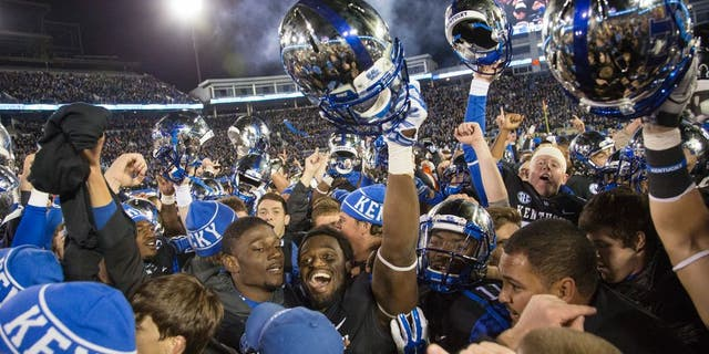 Fans and Kentucky players celebrate together on the field after Kentucky defeated South Carolina 45-38 in an NCAA college football game in Lexington, Ky., Saturday, Oct. 4, 2014. (AP Photo/David Stephenson)