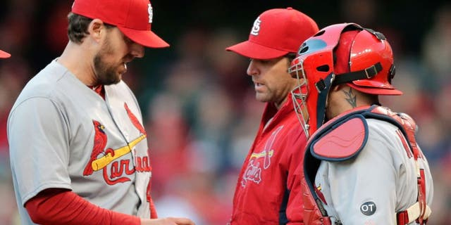 St. Louis Cardinals starting pitcher John Lackey, left, hands the ball off to manager Mike Matheny, center, as catcher Yadier Molina watches in the sixth inning of a baseball game against the Cleveland Indians, Wednesday, May 13, 2015, in Cleveland. Lackey pitched 5 1/3 innings and gave up five hits and two runs. (AP Photo/Tony Dejak)