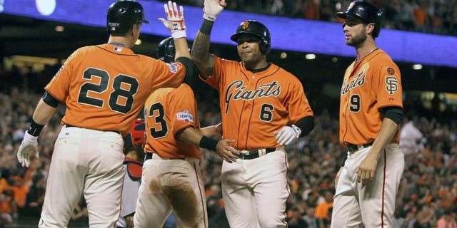 Aug 28, 2015; San Francisco, CA, USA; San Francisco Giants catcher Buster Posey (28) left fielder Nori Aoki (23) and first baseman Brandon Belt (9) greet right fielder Marlon Byrd (6) who hit a grand slam home run against the St. Louis Cardinals in the third inning of their MLB baseball game at AT&T Park. Mandatory Credit: Lance Iversen-USA TODAY Sports