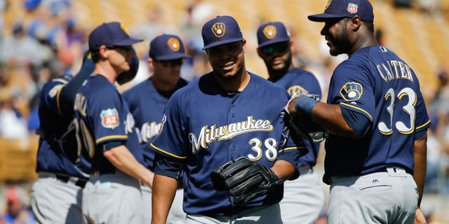 Milwaukee Brewers starting pitcher Wily Peralta, center, walks off the mound past Chris Carter, right, after he was relieved during the fourth inning of a spring training baseball game against the Los Angeles Dodgers Monday, March 14, 2016, in Phoenix.