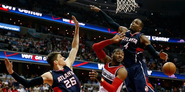 Washington Wizards guard John Wall, center, passes the ball between Atlanta Hawks guard Kyle Korver (26) and forward Paul Millsap (4) in the first half of Game 6 of the second round of the NBA basketball playoffs, Friday, May 15, 2015, in Washington. (AP Photo/Alex Brandon)
