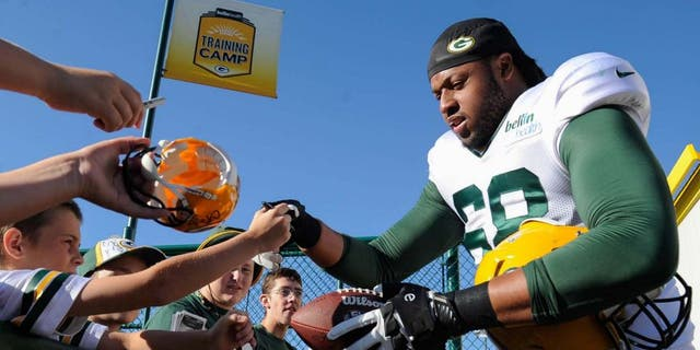 Green Bay Packers tackle Fabbians Ebbele signs autographs for fans during training camp on Aug. 3, 2015, at Ray Nitschke Field.