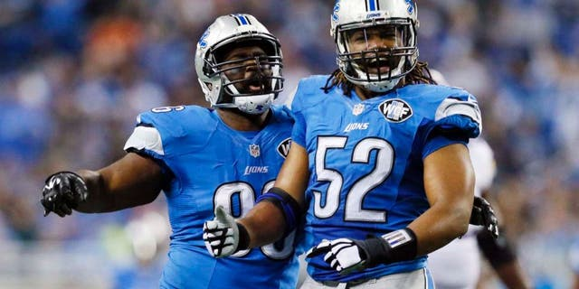 Detroit Lions defensive tackle Andre Fluellen (left) and defensive end Darryl Tapp react after their sack of Minnesota Vikings quarterback Teddy Bridgewater during the first half.