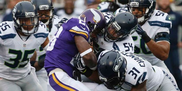 Minnesota Vikings running back Adrian Peterson is stopped by Seattle Seahawks defenders including linebacker Bobby Wagner (center) and strong safety Kam Chancellor (bottom right) in the first half of an NFL football game Sunday, Dec. 6, 2015 in Minneapolis.