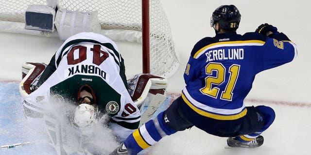 Minnesota Wild goalie Devan Dubnyk, left, smothers a puck as he is sprayed by St. Louis Blues' Patrik Berglund, of Sweden, during the third period in Game 2 of an NHL hockey first-round playoff series, Saturday, April 18, 2015, in St. Louis. The Blues won 4-1 to tie the series 1-1. (AP Photo/Jeff Roberson)